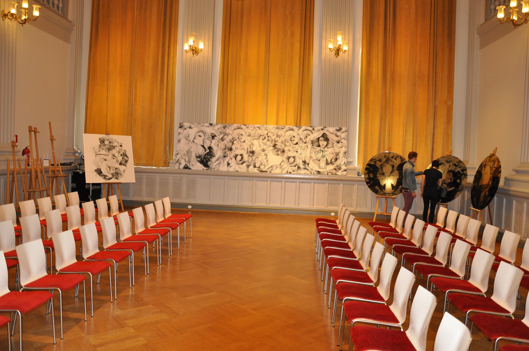 näytössali jossa taustalla Jenni Ritamäen maalauksia näytöksen teemasta